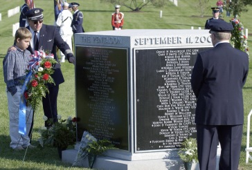 American Airlines (AA) pilot Captain (CAPT) James C. Condes, shows his son Christopher, the inscribed pilot's name of the ill fated flight 77, CAPT Charles Burlingame, prior to a memorial service at Arlington National Cemetery for the 184 victims of the September 11th, 2001, terrorist attack on the Pentagon.